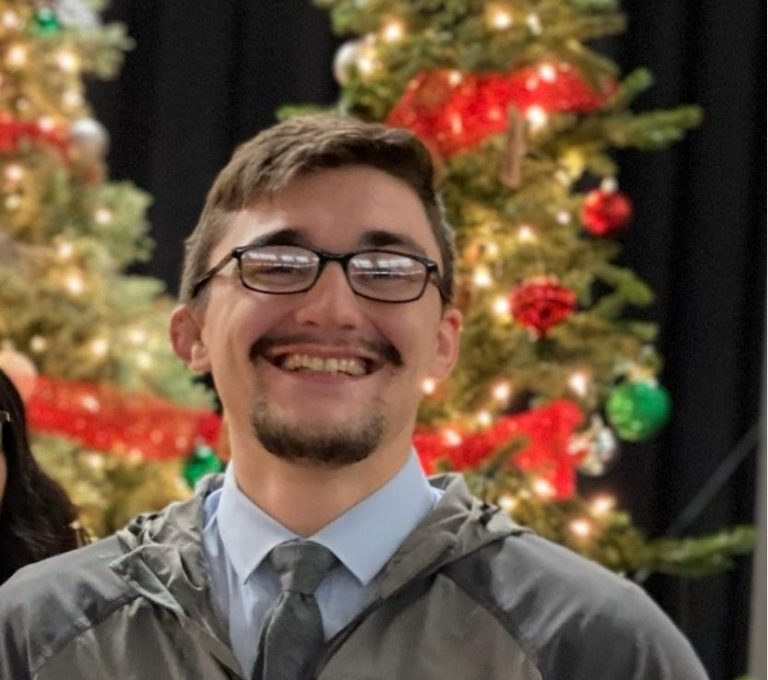 WOU student Adam Dryden smiles in front Christmas trees. He is wearing a gray zip-up jacket with a dress shirt and tie underneath.