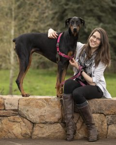 Student sitting on a stone fence, arm slung gently over her tall dog.
