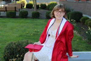 Student sits on concrete in red WOU robe, smiling with a green lawn in the background.
