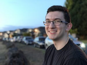 Student with glasses smiling at a side profile to the camera, a row of cars behind him.