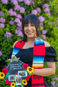 Student standing in front of a flowery hedge, holding a decorated graduation cap out to the camera. She is wearing a striped red, blue, yellow, and white sash around her neck.