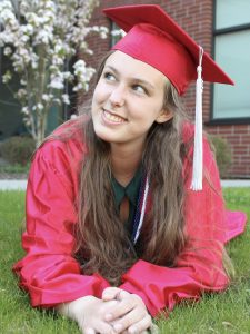 Student laying on lawn in red cap and gown, propped up on her elbows and smiling at the sky.