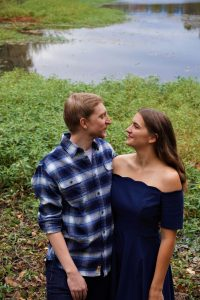 Student side-hugging her husband and looking into his eyes. They are both wearing blue and standing in front of a shallow pond.