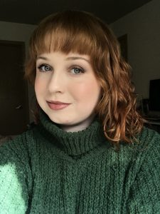 Student has red hair, is cast mostly in shadow, and is slightly smiling at camera while wearing a green sweater.