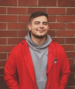 Student standing in front of brick wall, hands in his pockets, wearing a red WOU jacket, and smiling at camera.