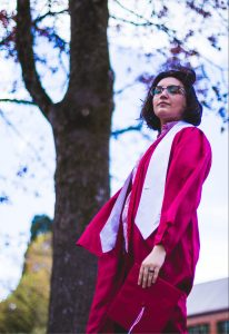 Student standing near tall tree, their side facing the camera. They are wearing WOU's red graduation gown.