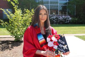 """Student in grad gown standing in sunshine, holding a decorated cap that reads """"Hija de immigrantes."""""""