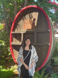Student standing in front of giant wooden barrels, trees behind her as well.