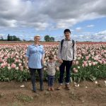 Two people and a child holding hands and standing in front of a field of flowers