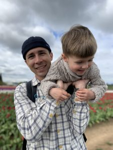 Student in white and black shite holding young boy over his shoulder, a field of tulips behind them.