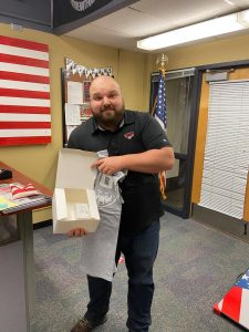 Student smiling and holding small box, an American flag partially visible behind him.
