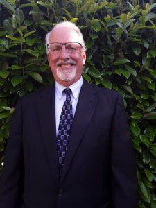 Dr. Jay Kenton smiling and wearing a dark suit