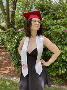 Student stands in front of bush, hands on her hips, as she wears a red grad cap and a WOU sash.