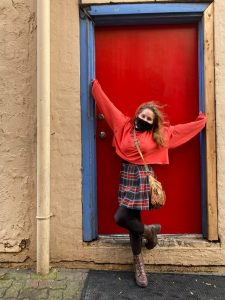 Student stands in outside doorway, red door closed behind her. She's stretching her arms out and up. The day seems sunny.