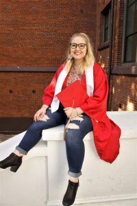 Student sits on stone rail, wearing red grad gown, holding red grad cap, and smiling at camera.