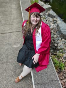 Student sitting on stone bench, looking up at camera and wearing WOU's red cap and gown.