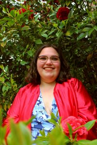 Student stands in front of tall bush wearing red grad gown. She's smiling directly at camera.