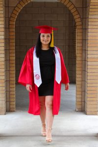 Student walks through brick archway wearing red grad cap and gown.