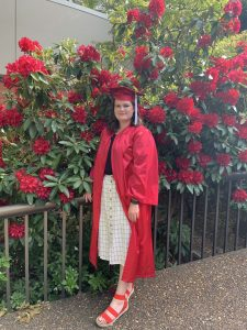 Student posing in red cap and gown, standing in front of big, red flowers.