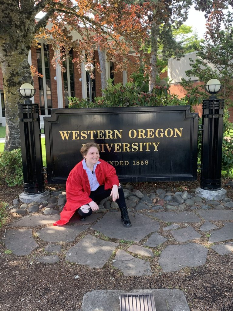Student in a red graduation robe crouching down and smiling in front of WOU sign