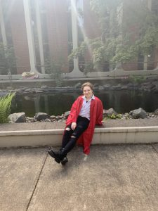 Student in a red graduation robe sitting on a curb and smiling
