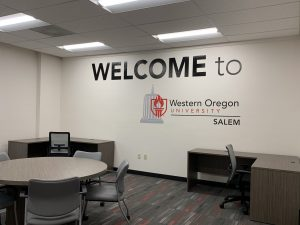 """Study space with several tables and chairs; the wall reads """"welcome to Western Oregon University Salem"""""""