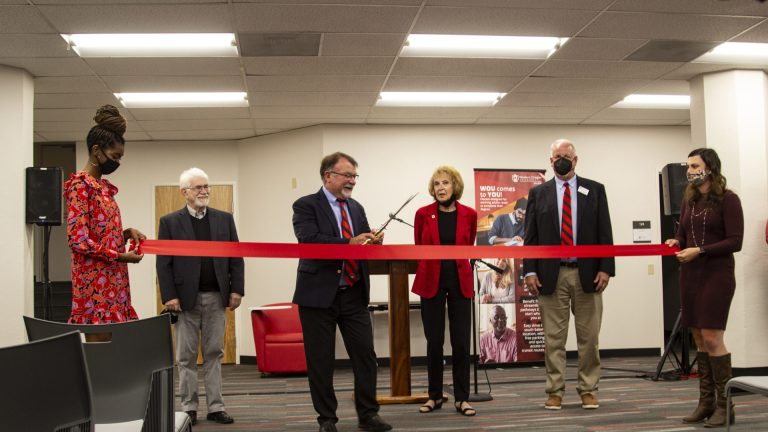 One person cutting a ribbon held up by two others. Three additional people in the background